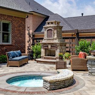 Modelo de piscinas y jacuzzis clásicos, pequeños, redondeados, en patio trasero, con adoquines de hormigón