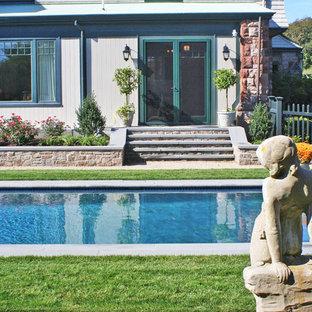 Imagen de piscina natural, tradicional, de tamaño medio, rectangular, en patio lateral, con adoquines de piedra natural