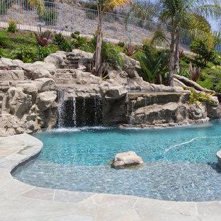 Modelo de piscina con tobogán natural, tropical, grande, a medida, en patio trasero, con adoquines de piedra natural