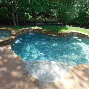 This is an example of a mid-sized country backyard custom-shaped natural pool in Atlanta with a hot tub and brick pavers.
