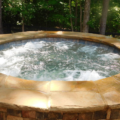 Example of a mid-sized mountain style backyard brick and custom-shaped natural hot tub design in Atlanta