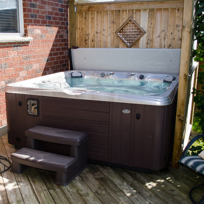 Hot tub - mid-sized traditional backyard custom-shaped aboveground hot tub idea in Other with decking