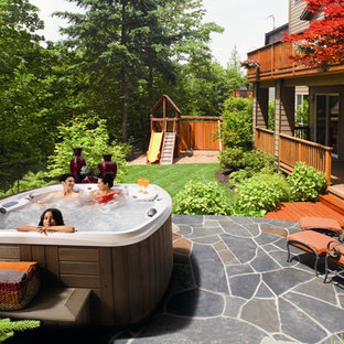 Mid-sized country backyard custom-shaped aboveground pool in Portland with a hot tub and natural stone pavers.