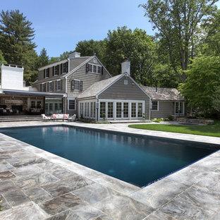 Klassischer Pool hinter dem Haus in rechteckiger Form mit Natursteinplatten in Bridgeport