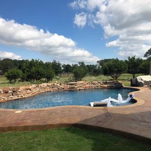 Diseño de piscina con fuente natural, tropical, de tamaño medio, a medida, en patio trasero, con entablado