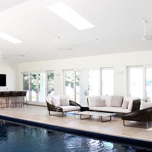 Ejemplo de casa de la piscina y piscina contemporánea, rectangular y interior, con adoquines de piedra natural