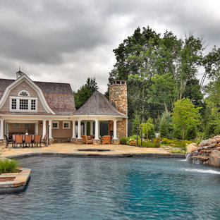 This is an example of a large traditional custom-shaped natural pool in New York with a pool house.