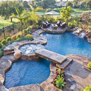 Idee per una grande piscina tropicale personalizzata dietro casa con una vasca idromassaggio e pavimentazioni in pietra naturale