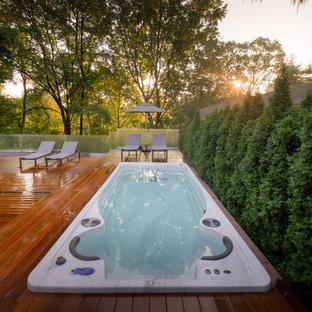Esempio di una piscina fuori terra design rettangolare di medie dimensioni e dietro casa con una vasca idromassaggio e pedane