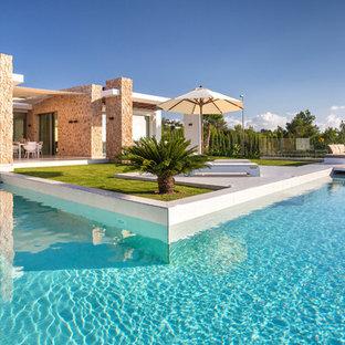 Modelo de piscina alargada, mediterránea, grande, en forma de L, con entablado