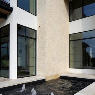 Foto de piscina con fuente alargada, moderna, de tamaño medio, rectangular, en patio trasero, con suelo de baldosas
