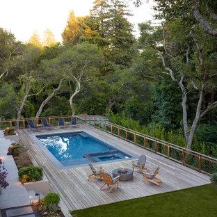 На фото: большой прямоугольный бассейн на заднем дворе в стиле модернизм с настилом с