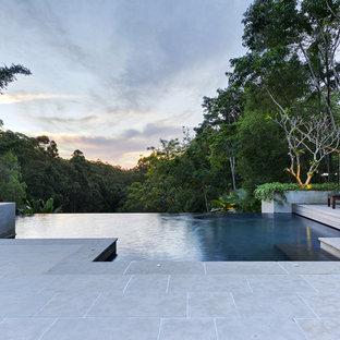 Foto på en stor tropisk infinitypool på baksidan av huset, med naturstensplattor