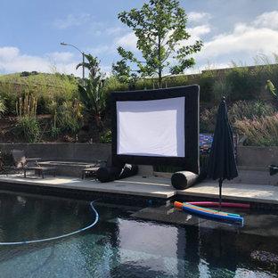 Réalisation d'une grand piscine hors-sol et arrière bohème rectangle avec un aménagement paysager autour d'une piscine et une dalle de béton.