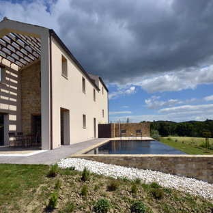 Bild på en lantlig rektangulär infinitypool längs med huset, med marksten i tegel