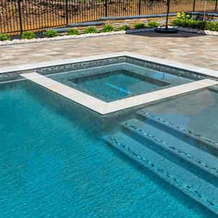 Réalisation d'un grand couloir de nage arrière minimaliste rectangle avec un bain bouillonnant et des pavés en brique.