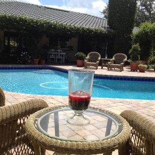 """Idee per una piscina tropicale a """"L"""" di medie dimensioni e dietro casa con pavimentazioni in mattoni"""