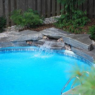 Foto de piscina con fuente tradicional, de tamaño medio, a medida, en patio trasero, con gravilla