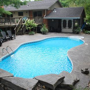 Immagine di una grande piscina chic personalizzata dietro casa con lastre di cemento