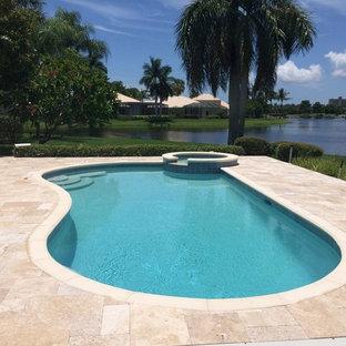 Modelo de piscinas y jacuzzis tropicales, de tamaño medio, tipo riñón, en patio trasero, con suelo de baldosas