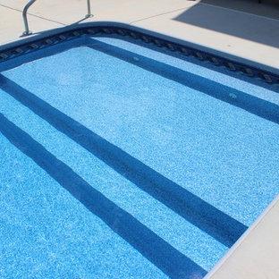 Immagine di una grande piscina minimalista dietro casa con cemento stampato