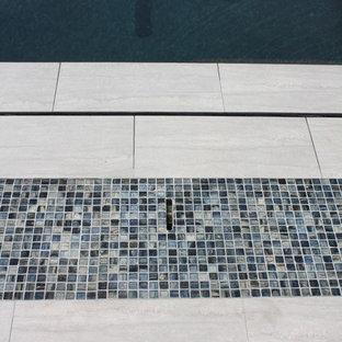 Modelo de piscina con fuente infinita, actual, extra grande, a medida, en patio trasero, con suelo de baldosas