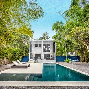 Diseño de piscina alargada, contemporánea, en forma de L, en patio trasero, con losas de hormigón