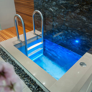 Modern indoor rectangular pool in Vancouver with a hot tub and tile.