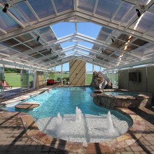 Idee per una grande piscina coperta monocorsia chic rettangolare con una vasca idromassaggio e pavimentazioni in cemento