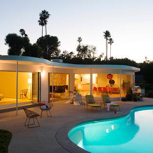 """Idee per una grande piscina moderna a """"C"""" dietro casa con una dépendance a bordo piscina e lastre di cemento"""