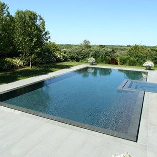 Ejemplo de piscinas y jacuzzis infinitos, actuales, a medida, con adoquines de piedra natural