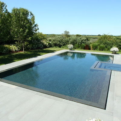 Example of a trendy stone and custom-shaped infinity hot tub design in New York