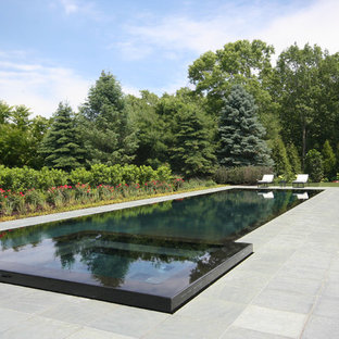 Ejemplo de piscina infinita, clásica renovada, grande, rectangular, con adoquines de piedra natural