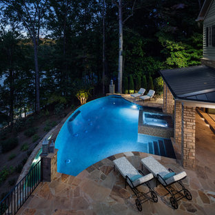 Inspiration for a huge timeless backyard brick and custom-shaped infinity pool house remodel in Atlanta