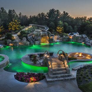 Idee per un'ampia piscina a sfioro infinito personalizzata dietro casa con un acquascivolo e pavimentazioni in pietra naturale