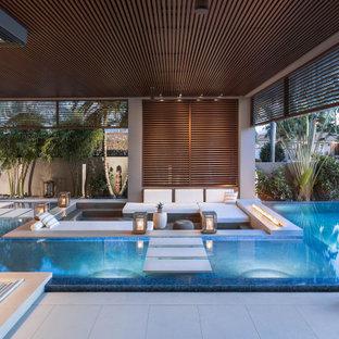 Esempio di un'ampia piscina a sfioro infinito moderna personalizzata dietro casa con pedane