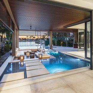 Réalisation d'une très grand piscine sur une terrasse en bois à débordement et arrière minimaliste sur mesure.