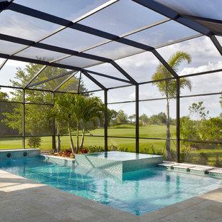 """Foto di una grande piscina chic a """"L"""" dietro casa con pavimentazioni in pietra naturale e una vasca idromassaggio"""