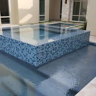 Ejemplo de piscinas y jacuzzis infinitos, minimalistas, grandes, rectangulares, en patio trasero, con suelo de hormigón estampado