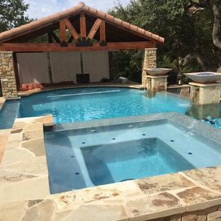 Immagine di una grande piscina a sfioro infinito rustica personalizzata dietro casa con una vasca idromassaggio e pedane