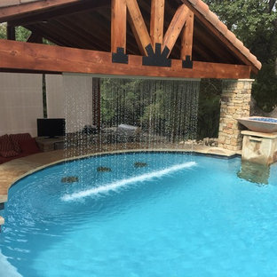 На фото: большой бассейн-инфинити произвольной формы на заднем дворе в стиле рустика с джакузи и настилом с