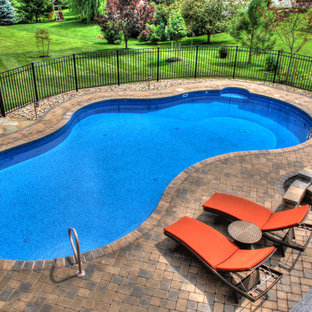 Foto de piscina alargada, clásica, grande, tipo riñón, en patio trasero, con adoquines de hormigón