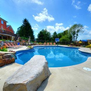 """Ispirazione per una grande piscina monocorsia chic a """"C"""" dietro casa con un acquascivolo e lastre di cemento"""
