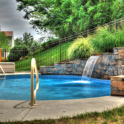 Example of a small tuscan backyard concrete and kidney-shaped lap pool design in Other