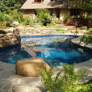 Modelo de piscina ecléctica, de tamaño medio, a medida, en patio trasero, con adoquines de piedra natural