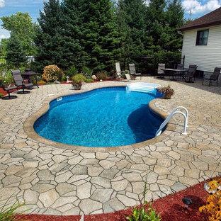 Imagen de piscina clásica, de tamaño medio, tipo riñón, en patio trasero, con adoquines de hormigón