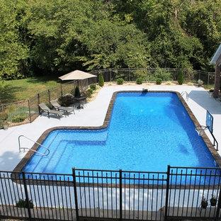 """Esempio di una grande piscina stile americano a """"L"""" dietro casa con lastre di cemento"""