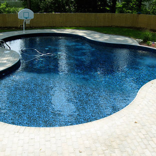 Modelo de piscina alargada, tradicional, de tamaño medio, a medida, en patio trasero, con adoquines de ladrillo