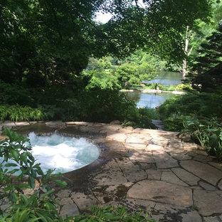 Ejemplo de piscina natural, clásica, pequeña, redondeada, en patio lateral, con adoquines de piedra natural