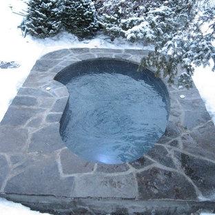 Idées déco pour une piscine arrière scandinave de taille moyenne et sur mesure avec un bain bouillonnant et des pavés en pierre naturelle.